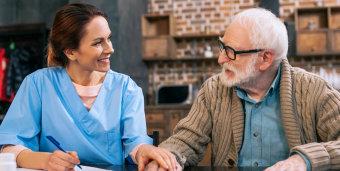 senior man talking to a caregiver about medication