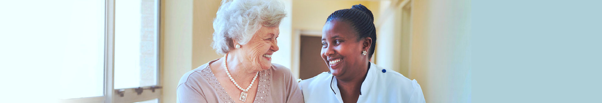 nurse and senior woman smiling to each other