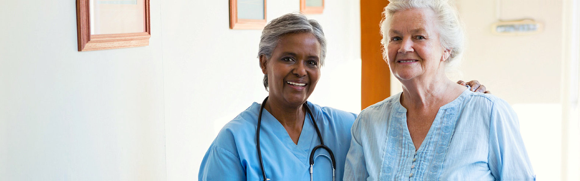 nurse and senior woman inside the house smiling