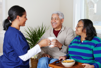 caregiver and an elder couple smiling